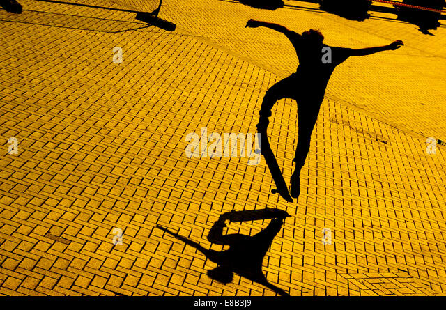 A skateboarder at dusk makes a jump casting a shadow on the brick paved surface. - Stock-Bilder