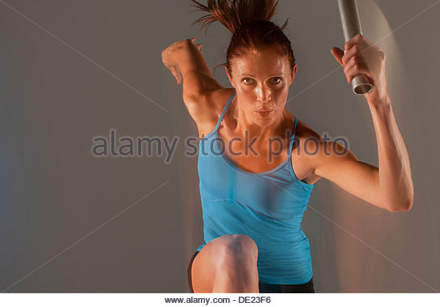 Blurred view of athlete running with baton - Stock Image