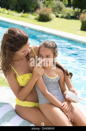 Mother applying sunscreen to daughter's nose - Stock Image
