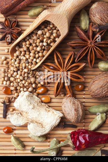 Spices and herbs over bamboo mat - Stock Image