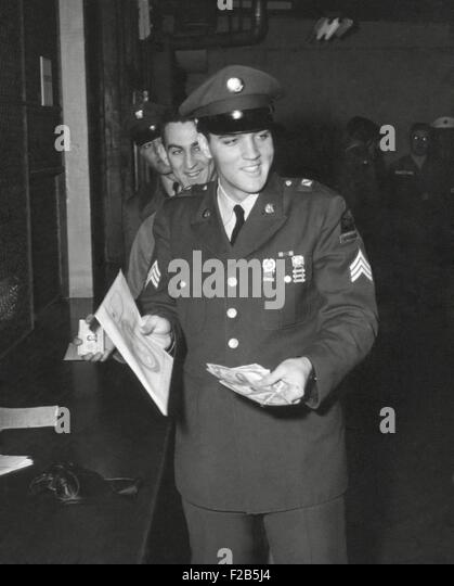 Sgt. Elvis A. Presley, 32nd Armored, 3rd Armored Div. collecting his last pay as he re-enters civilian life. March - Stock Image