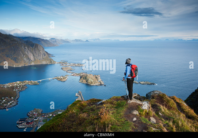 Female hiker enjoys spectacular view over mountains and fjords from Reinebringen, Lofoten islands, Norway - Stock-Bilder