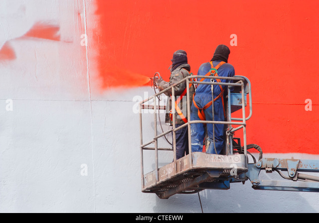 Spray painting ship in dry dock - Stock Image