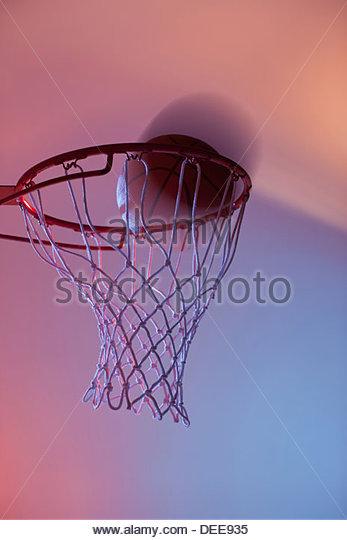 Basketball on rim of hoop - Stock Image