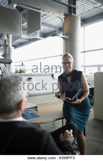 Businessman and businesswoman talking,meeting in office cubicle - Stock Image