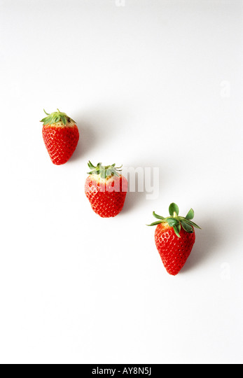 Three strawberries in a diagonal row - Stock Image