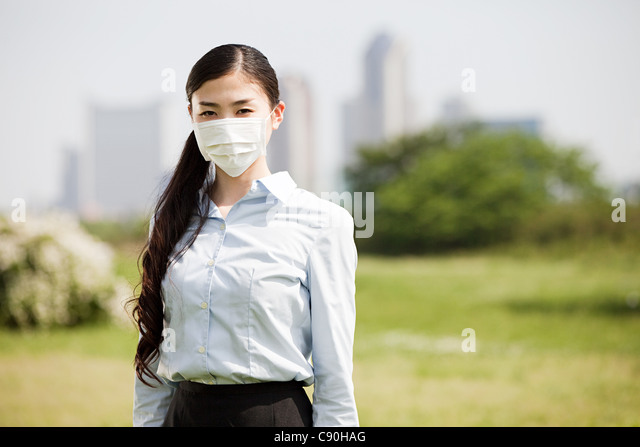 Young businesswoman wearing pollution mask - Stock Image