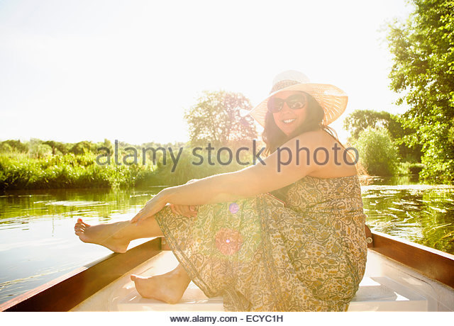Hispanic woman sitting in canoe on river - Stock Image