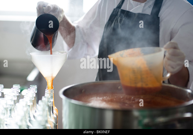 Close up of a factory worker pouring tomato sauce through a funnel into bottles - headless - Stock-Bilder