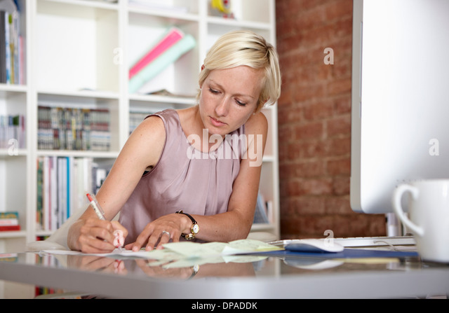 Mid adult woman making notes at desk - Stock Image