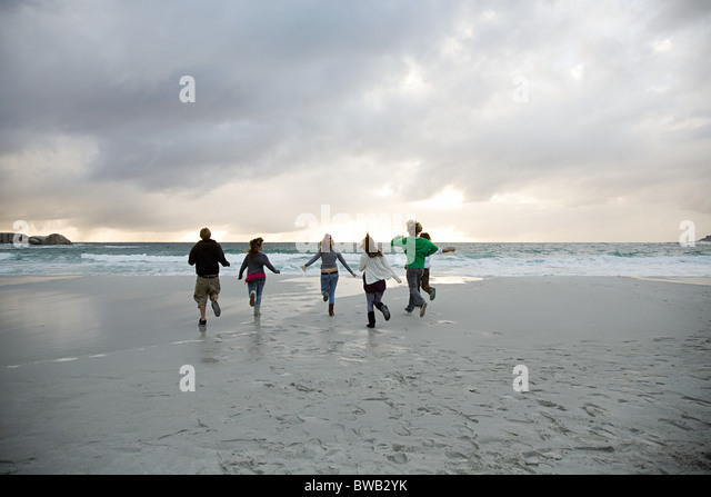 People running on beach - Stock Image