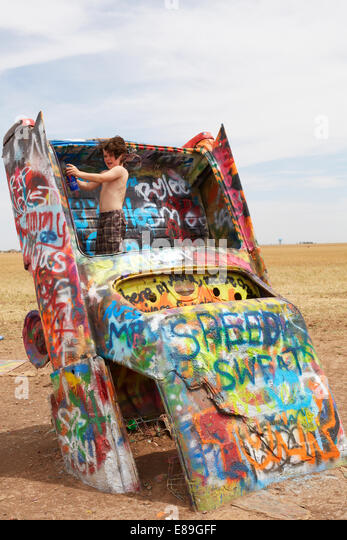 Boy standing on car at Cadillac Ranch - Stock-Bilder