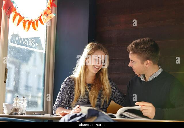 Young couple on date in cafe reading magazine - Stock-Bilder