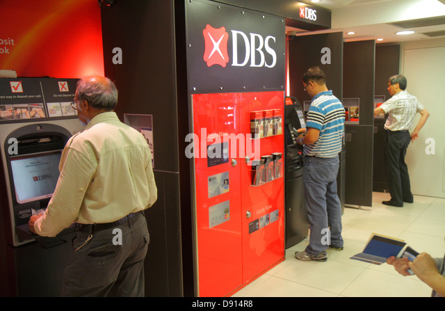 Singapore Raffles Place MRT Station ATM automated teller machine DBS Asian man using self-service banking bank money - Stock Image