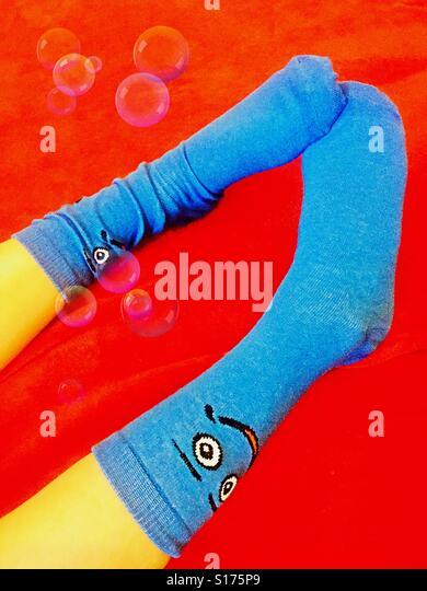Child wearing smiley face socks - Stock-Bilder