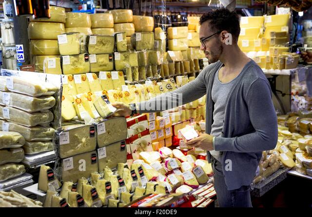 Young man selecting cheese in delicatessen market stall, Sao Paulo, Brazil - Stock Image