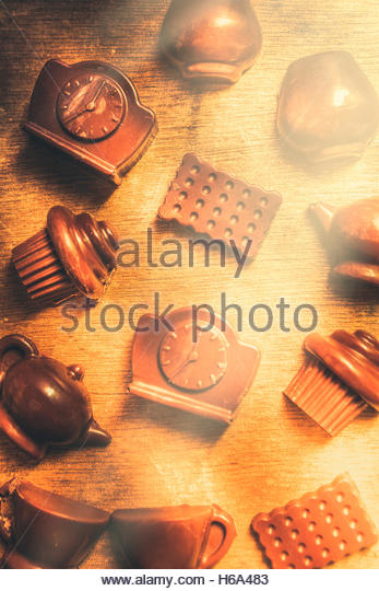 Creative coffee snacks still life with cups of chocolate tea with clocks blocks dark choc and cupcakes - Stock Image