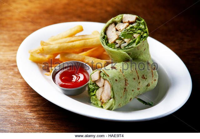 Grilled curry chicken with greens wrap and French fries - Stock Image