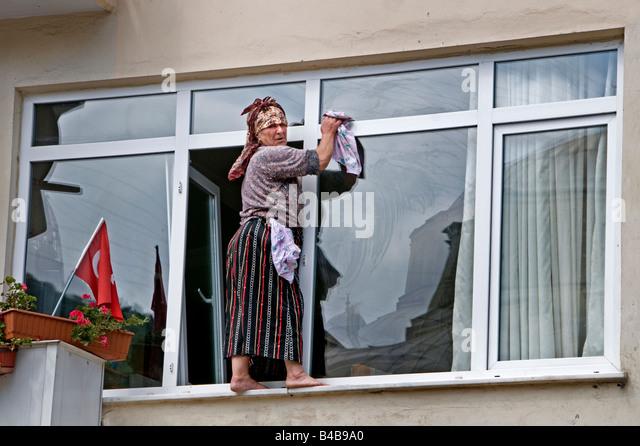 Istinye cleaning woman window windows cleaners dangerous, perilous, risky, hazardous - Stock Image