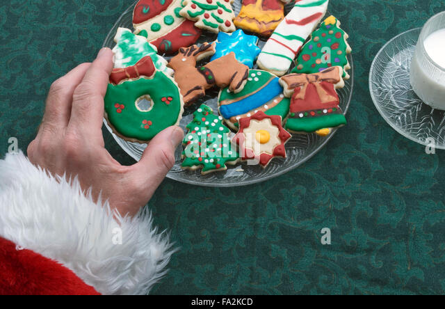 Santa Selecting A Christmas Cutout Cookie Off Of Plate, With Glass Of Milk - Stock Image