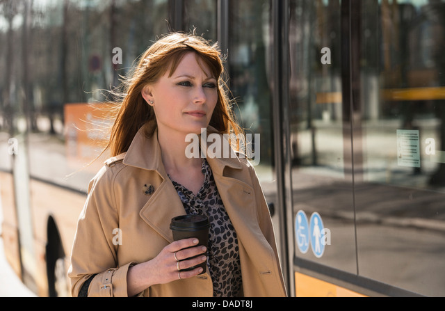 Woman with takeaway coffee next to city bus - Stock-Bilder