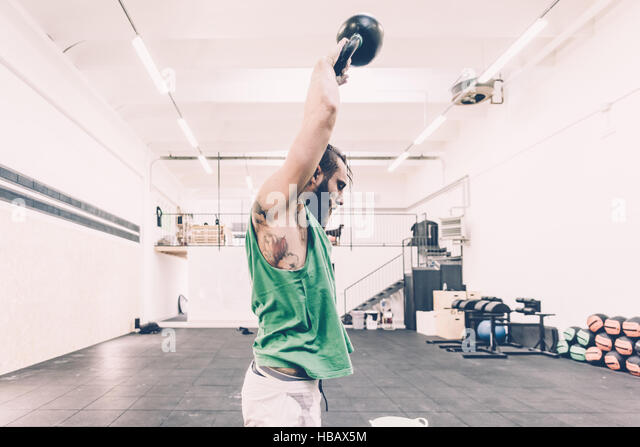 Young male cross trainer weightlifting kettlebell in gym - Stock Image
