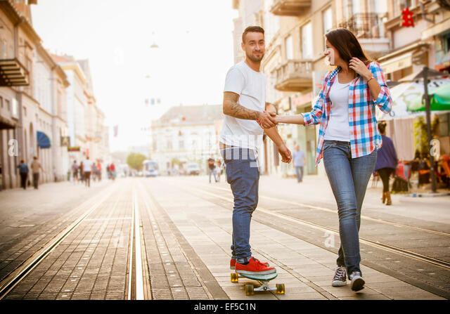 Young man skateboarding on city street, woman assisting - Stock Image