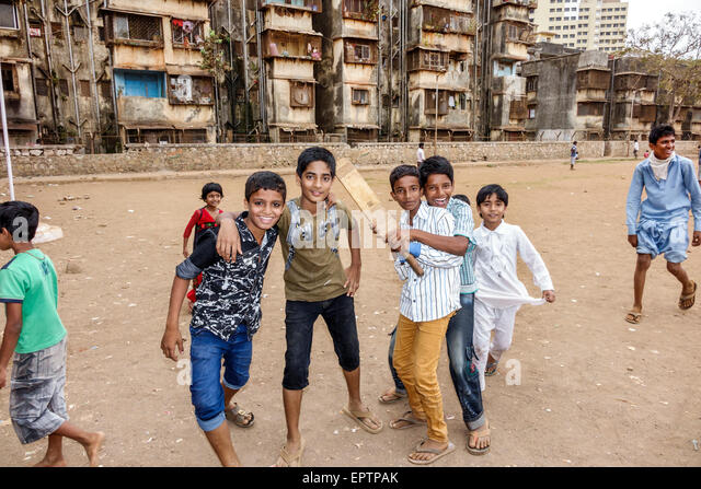 India Asian Mumbai Dharavi Shahu Nagar Road slum dirt lot cricket field pitch boy friends playing bat - Stock Image