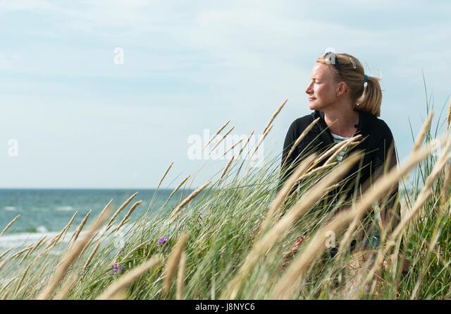Woman looking at sea - Stock-Bilder