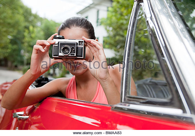Young woman taking photograph in convertible car - Stock Image