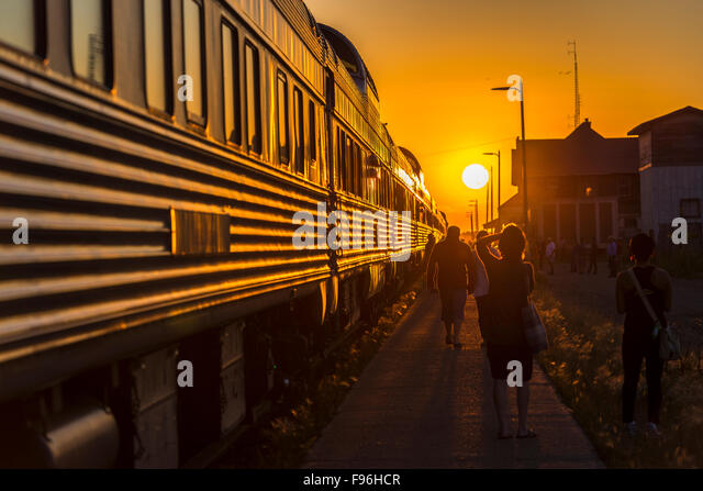 Sun setting in front of passenger train stopped in the town of Melville in Saskatchewan, Canada. - Stock-Bilder