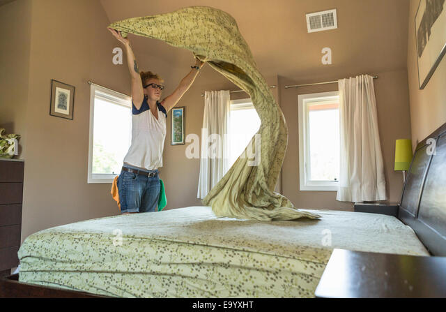 Young woman cleaning bedroom with green cleaning products - Stock-Bilder