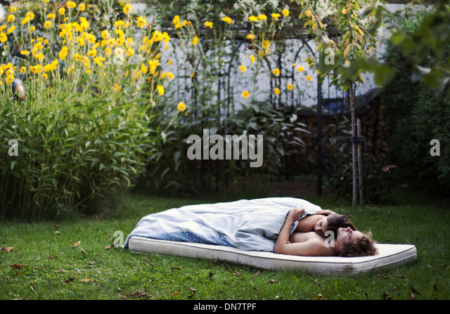 Loving couple lies asleep on a mattress in the garden - Stock Image