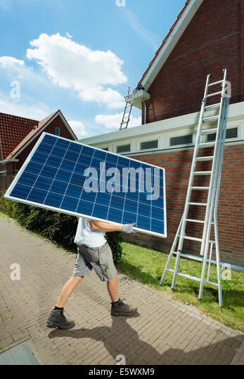 Worker carrying solar panel for roof of new home, Netherlands - Stock-Bilder