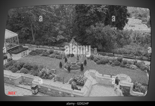 CCTV concept image 'capturing' a public garden and showing images of persons who are being monitored and - Stock Image