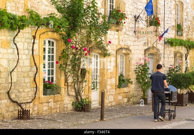 the Mairie in Monpazier with postman, Pays de Bergerac, Périgord, Dordogne, Aquitaine, France - Stock Image