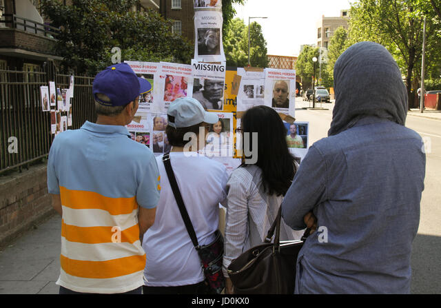 London, UK. 16th June 2017 - A group of people stand by a board with missing person posters on 17 June. At least - Stock Image