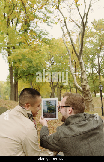 Gay couple photographing with digital tablet - Stock Image