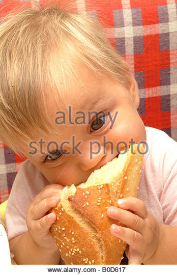 Baby Toddler ENJOYING a SANDWICH child bread cheese eating bread sandwiches eat eating - Stock-Bilder