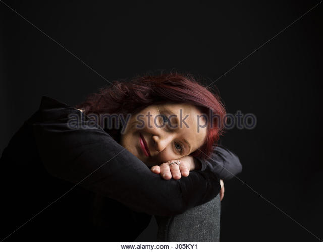 Portrait smiling woman with red hair leaning on chair against black background - Stock Image