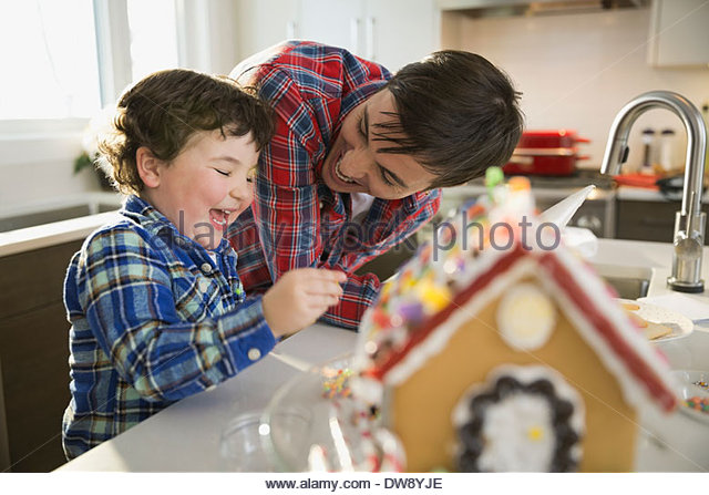 Father and son decorating gingerbread house together - Stock Image