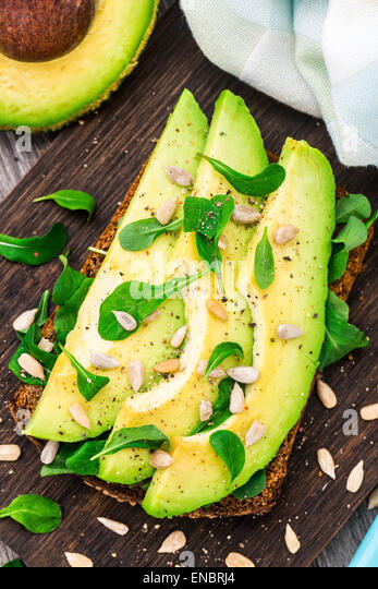 Avocado sandwich with arugula and sunflower seeds - Stock Image