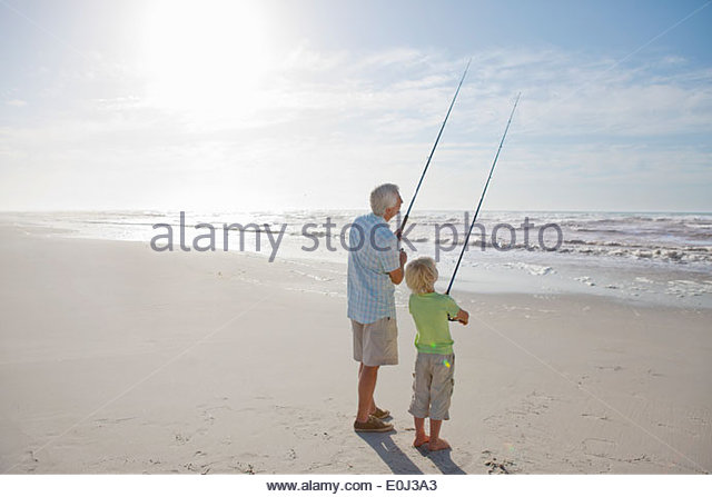 Grandfather and grandson fishing on sunny beach - Stock Image