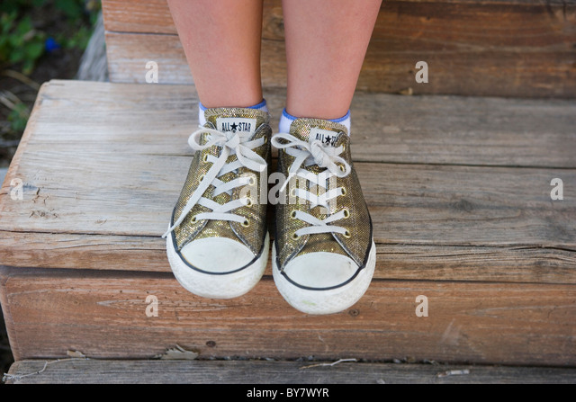 close up of a girl wearing glitter gold converse all star sneakers - Stock Image