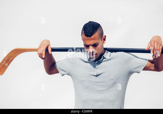 Young man with shaved hair holding hockey stick on his shoulders in front of white background - Stock Image