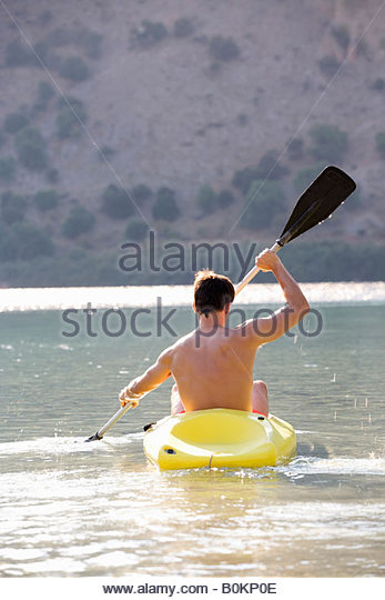 A man canoeing on a lake - Stock Image