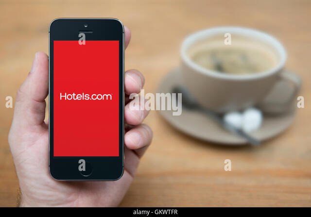 A man looks at his iPhone which displays the Hotels.com logo, while sat with a cup of coffee (Editorial use only). - Stock Image