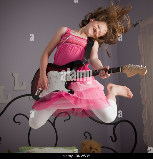 Young girls playing guitar on her bed - Stock Image