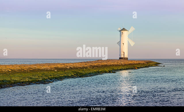 Sunrise over Baltic Sea coast, lighthouse in Swinoujscie, Poland. - Stock Image