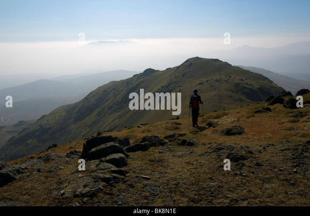 A walker on the summit of Arenig Fawr , in the Arenig hills, near Trawsfynydd, Snowdonia, North Wales, UK - Stock Image